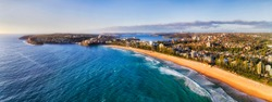 Long strip of clean yellow sandy beach of Manly - part of Sydney famous Northern Beaches seen from mid-air with distant Sydney harbour and Manly waterfront.