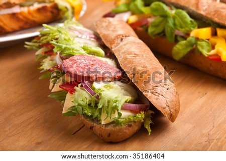 long sub sandwiches with salami on wooden table - stock photo