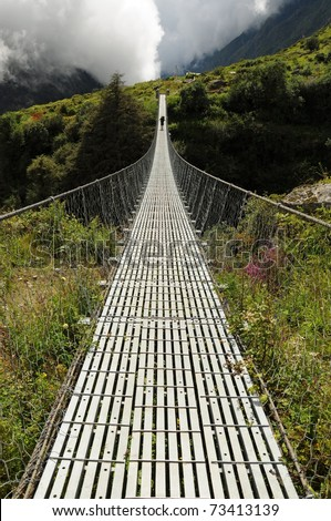 Long suspension foot bridge over deep valley in mountains, Himalaya, Nepal