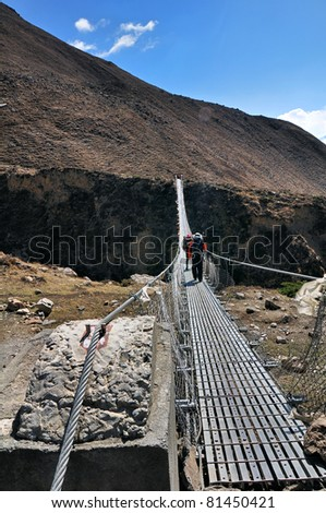 Long suspension foot bridge with silhouette of walking trekkers in mountains, Himalaya, Nepal - stock photo