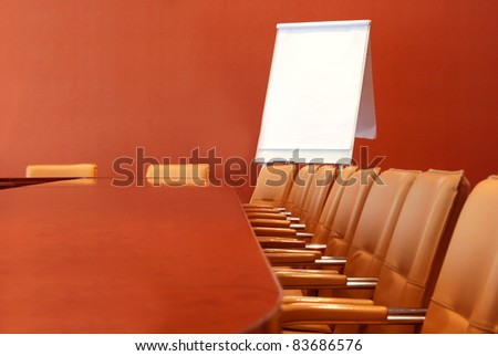 Long table for meetings with the chairs around the perimeter - stock photo