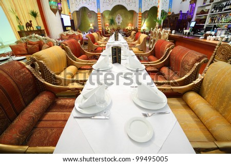 long table with white tablecloth and serving in eastern luxury restaurant - stock photo