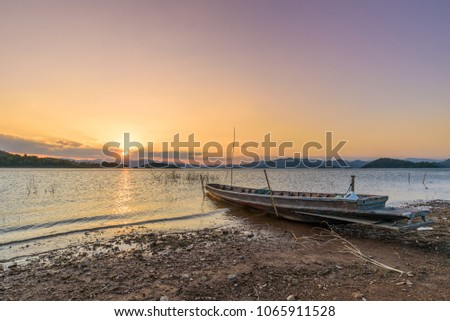 Long-tail Boat docking on the shore during sunset at Kaeng Krachan Dam, Phetchaburi Province, Thailand