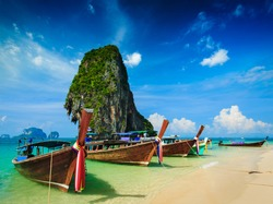 Long tail boat on tropical beach with limestone rock, Krabi, Thailand