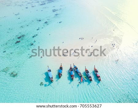 Long tail boats at sand bar beach with crystal clear water of the tropical island in Thailand