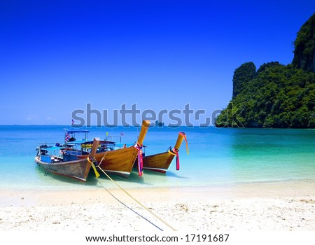stock photo : Long tailboats by the shore at Hong Island, Krabi Thailand against beautiful clear blue sky