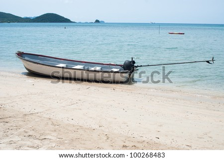 Long-tailed boat on the beach and the blue sea.