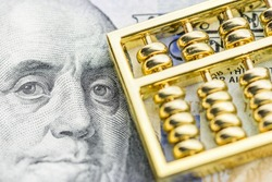 Long term investment for sustainable dividend growth, financial concept : Golden abacus on US dollar note, depicts investor invest or makes a saving plan in assets for capital gain and tax incentives