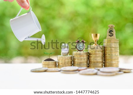Long-term investment for sustainable growth, financial concept : Hand pours water from a watering can, small tree, saving jar, clock, trophy cup of success / winner prize reward, US dollar bag on coin