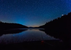 Long time exposure night landscape with starry sky above a mountain lake, Beglik dam in Rhodopi Mountains, Bulgaria