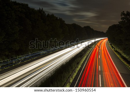 long time exposure on a highway with car light trails and cloudy sky