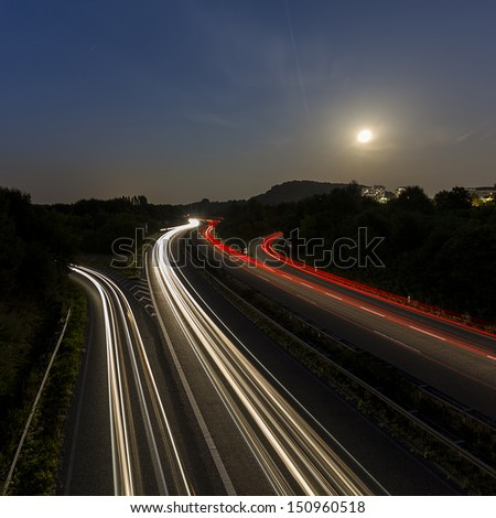 long time exposure on a highway with car light trails and moon in the sky