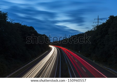long time exposure on a highway with car light trails at blue hour