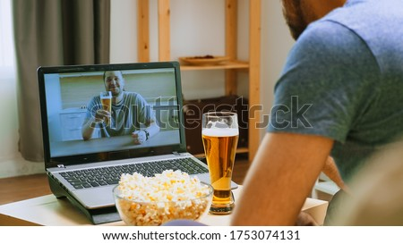 Long time friend talking on video call and drinking beer in time of global pandemic.