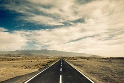 long way black asphalt road in the middle of the desert. travel and discover lost places concept for wanderlust people. straight white lines and infinite journey feeling in the nature