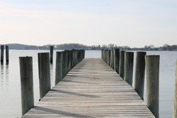 Long weathered wooden dock pier in coastal seaside harbor beach in winter