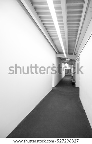 Shutterstock Long White Corridor.White Exhibition Hall.Technical Corridor In Large Building.Emergency exit.Corridor Exit Lighting.White Corridor With Empty Wall.
