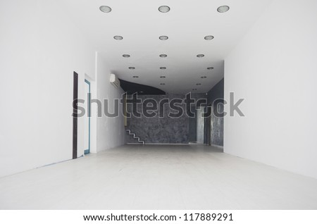 Long white corridor with the door at the end and left.