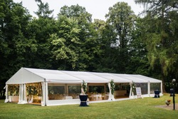 Long white tent for wedding party in the woods.