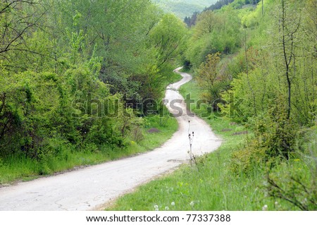 Long winding dirt road in the Balkan Mountains in Bulgaria in the spring.