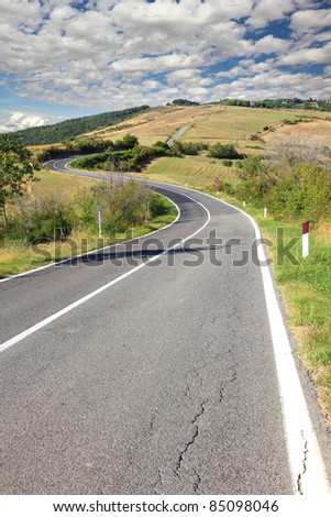 long winding road trough tuscany hills