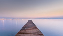 Long wood wharf on a lake at sunset, Empty pier in calm water,