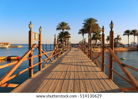 Long wooden boardwalk with lamposts on a sunny day in Hurghada, Egypt #514130629