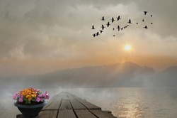 Long wooden bridge and flower pot with lake in the evening
