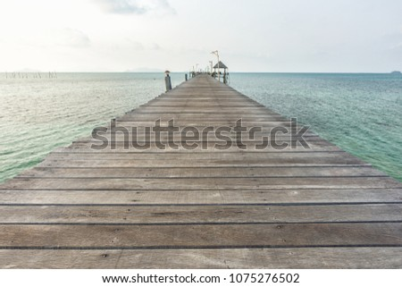 Long wooden bridge go to pavilion on the sea in beautiful tropical island, Thailand.