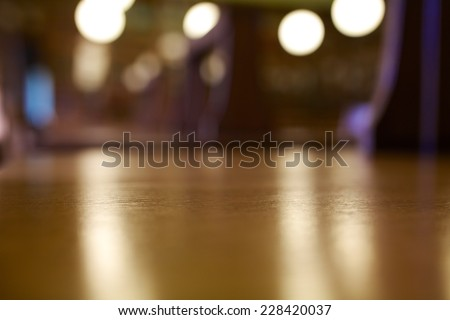 Long wooden desks at a old library with a blur background.