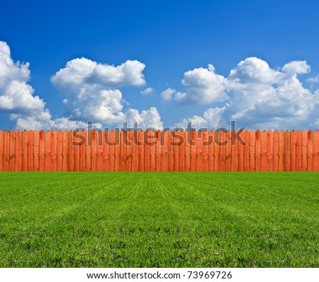 long wooden fence in a green field