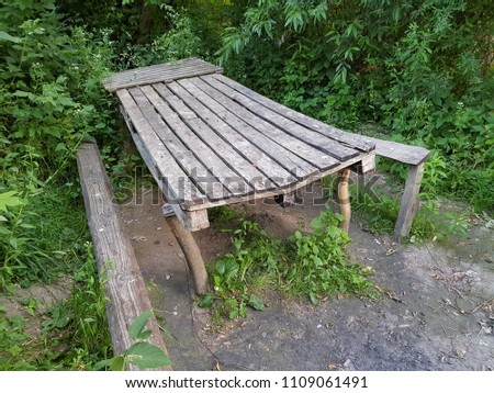 Long wooden old table and old benches in the forest #1109061491