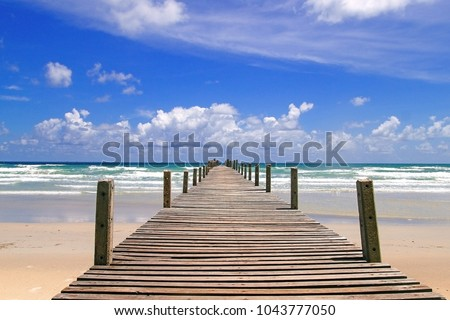 Long wooden pier (bridge) extents from beach to turquoise wave sea. Deep Blue cloudy sky after the big storm. Expectation to success dreams,Travel and summer Vacation, Freedom and youth Concept.