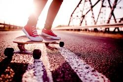 longboard  girl  on the street at beautiful summer evening, long board