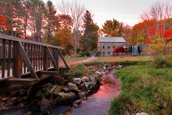Longfellow's  Wayside Inn Grist Mill with water wheel and cascade water fall in Autumn at sunrise, Sudbury Massachusetts USA