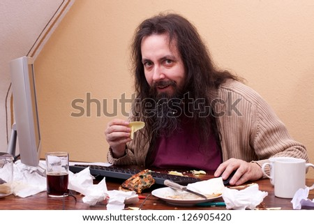 longhaired unkempt man is sitting at the computer