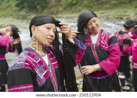 LONGJI, CHINA - MAY 06, 2009: Unidentified women brush and style hair on May 06, 2009 in Longji, China. Red Yao women living in Longji Yao village have one of the longest hair in the world.