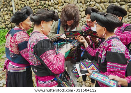 LONGJI, CHINA - MAY 06, 2009: Unidentified women sell souvenirs to a tourist in Longji, China. Women of Red Yao people living in Longji Yao village have one of the longest hair in the world.
