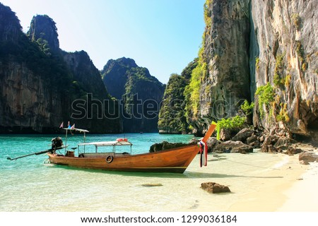 Longtail boat anchored by secluded beach on Phi Phi Leh Island, Krabi province, Thailand. This island is part of Mu Ko Phi Phi National Park.