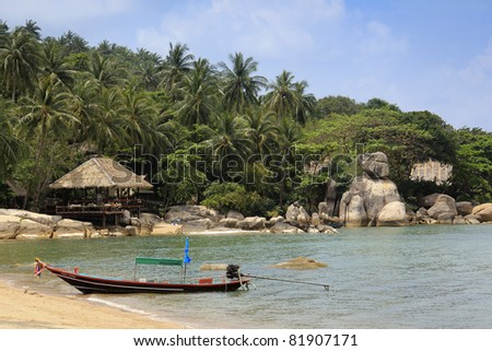 longtail boat on beach in front of resort built into the rock formations and jungle of koh tao in the gulf of thailand