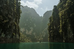 Longtail boats in a scenic scenery on a lake in the Khao Sok Nationalpark in Thailand