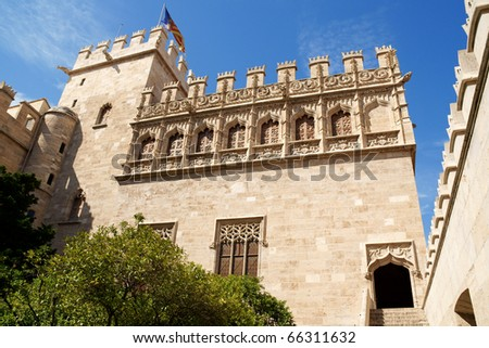 Lonja de la Seda of Valencia in Spain and the valencian flag. View from the garden. This small complex of late gothic buildings, originally was used to trade silk.