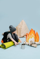 Lonley little boy un a cap sitting next to a fake campfire with paper flames and birch logs next to an improvised tent, made from packing paper. He's acting a scene, getting warm over blue background
