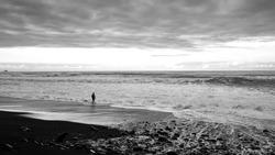 Lonley ocean beach Madeira, men standing in the water