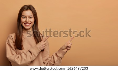 Look, advertise here! Dark haired pretty woman with appealing smile gives positive attitude towards good deal, expresses her recommendation while pointing on right side, wears brown sweater.