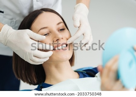 Look at me. Attractive caucasian lady checking her beautiful smile in mirror after stomatological treatment. Satisfaction of the visit stomatologist Foto stock ©