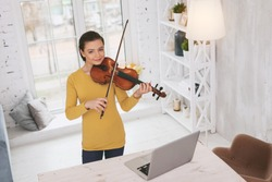 Look at me. Beautiful brunette keeping smile on face while playing the violin