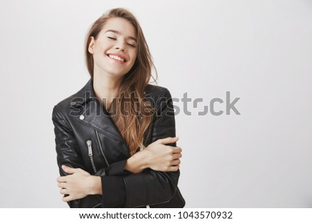 Look at that beauty and youth. Portrait of modern attractive feminine woman holding herself with crossed hands, tilting head up, smiling with closed eyes, feeling tender and sensual, enjoying spring #1043570932