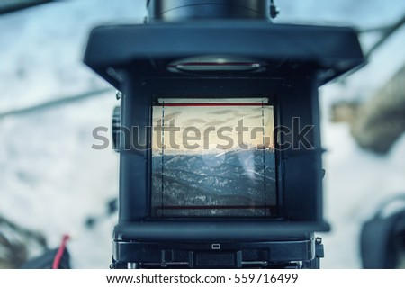 look at the mountain scenery through the viewfinder of an old film camera