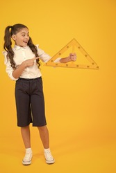 Look at the triangle with two equal sides. Happy little schoolgirl holding triangle on yellow background. Cute small kid smiling with geometric triangle for geometry lesson. Having lesson in triangle.